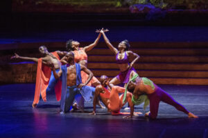 Dancers from @lula_washington_dance_theatre company posed in colorful costumes.