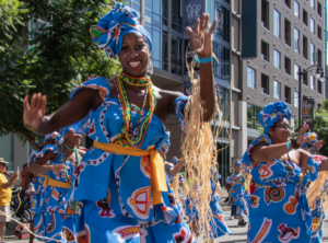 Black female @viverbrasildance dancer performing in the streets of downtown Los Angeles in a bright blue and ethnic outfit.
