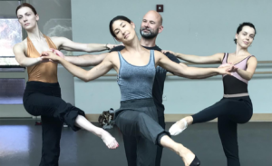 Dancers from @luminarioballet supporting female dancer while she balances in attitude devant.
