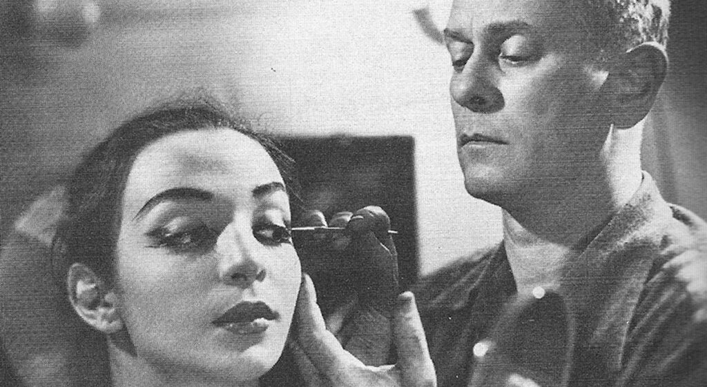 Lester Horton applying makeup to a dancer in black and white.