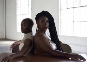 Two female black dancers posed back to back.
