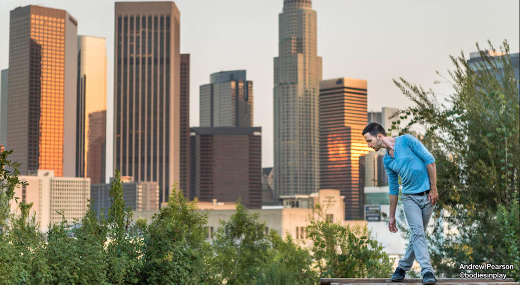 Andrew Pearson from @bodiesinplay leaning with DTLA in background.