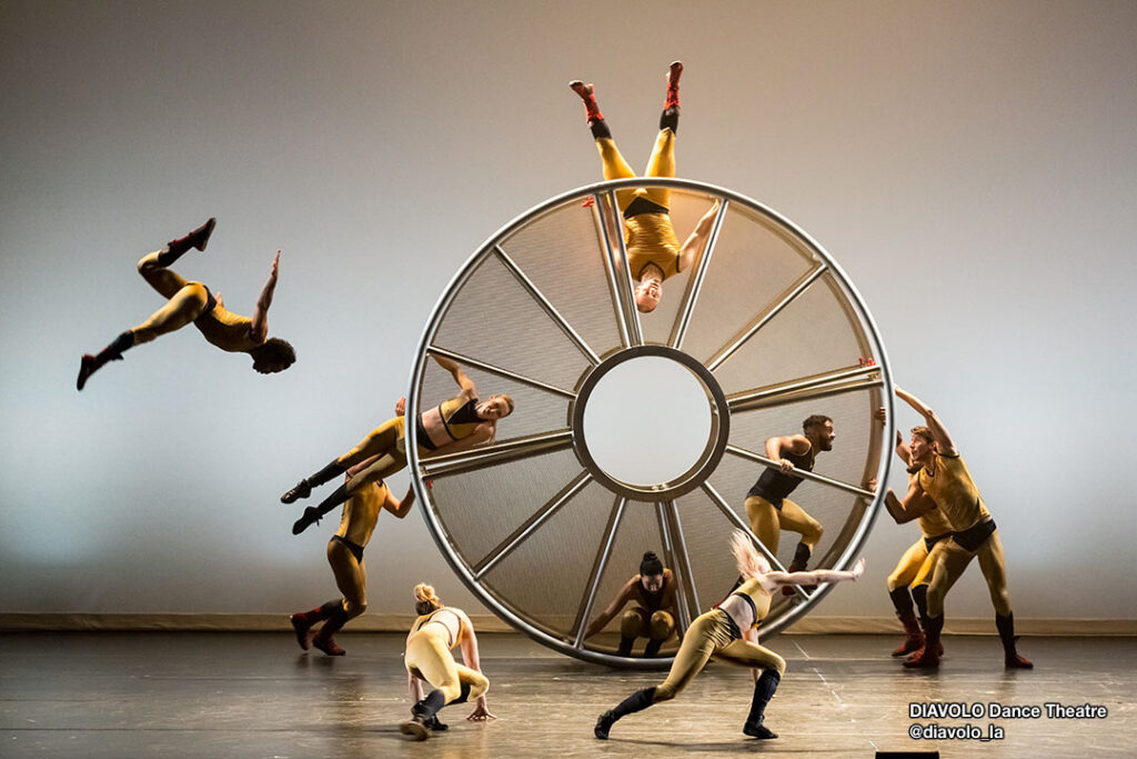Dancers from @diavolo_la company performing mid-air on spinning wheel.