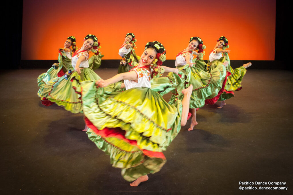 Female dancers from @pacifico_dancecompany holding bright green skirts.