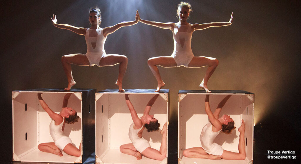 Dancers from @troupevertigo company on stage, three in boxes and two above in plie second position forced arch.