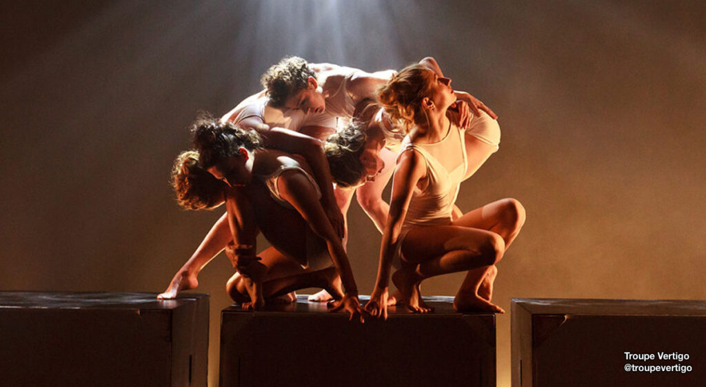Dancers from @troupevertigo clumped on stage and huddled around one another.