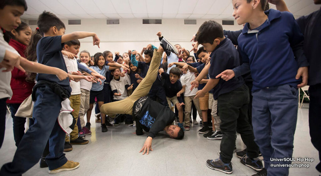 Breakdancer from @universoulhiphop in a breaking freeze, as children in circle point at him.