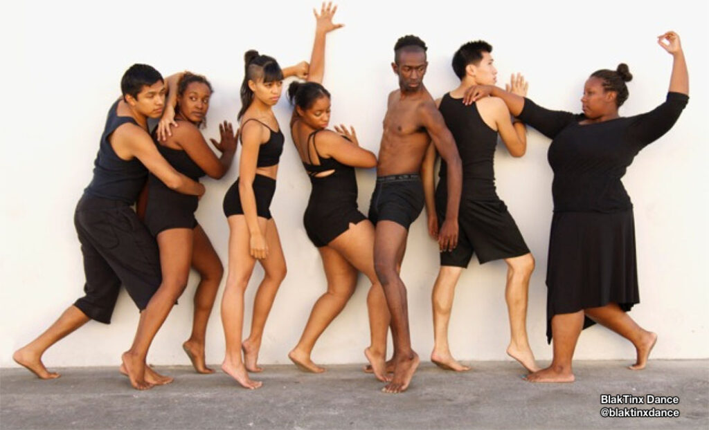 Dancers from @blaktinxdance posed against white wall at different levels.