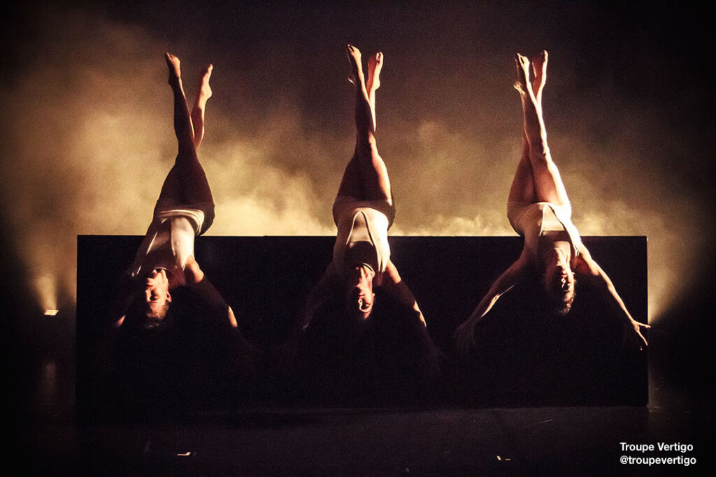 Three @troupevertigo dancers upside down with legs crossed and arms extended.